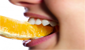 A woman biting into a slice of orange
