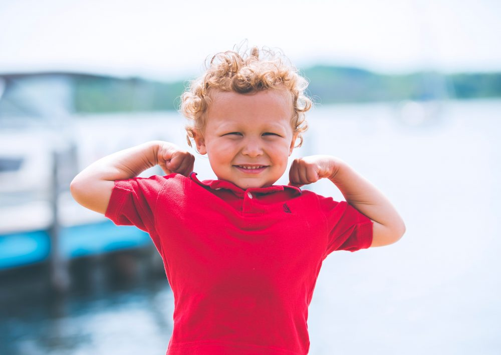 A child flexes his arms to show strength