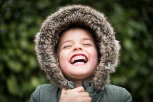 A child laughing hard in a parka coat