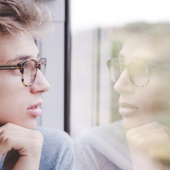 Young male staring out window deciding on Invisalign vs. braces.