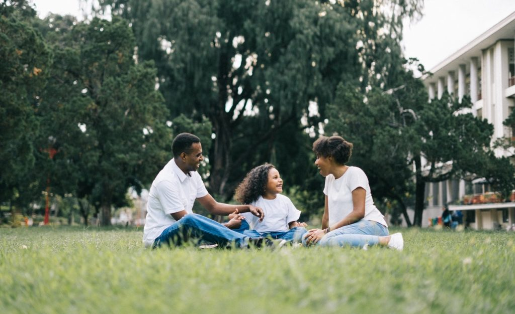 father and mother sitting with daughter in grass