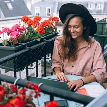 Woman in hat sitting outside smiling at her laptop