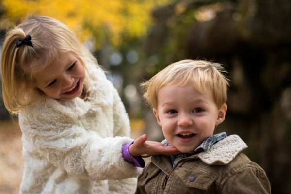 Young, toddler-aged sister and her brother smiling at camera.