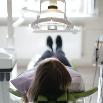 Woman laying in dentist chair for appointment.