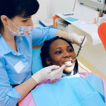 Woman receiving teeth-whitening services from her dental care team.