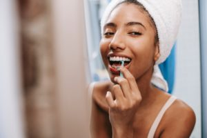 Young woman flossing her teeth and smiling.