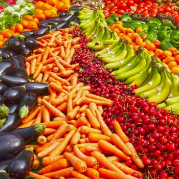 Healthy foods laid out in a rainbow.
