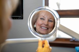 Woman looking in a small circle mirror, looking at her teeth.