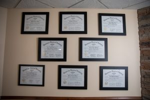 A wall with 8 degrees in plaques.
