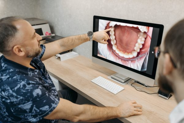 A dentist showing a patient a set of teeth displayed on a computer.