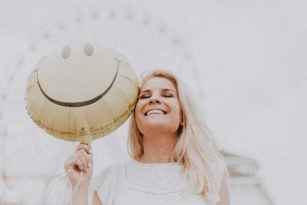 A smiling woman. Request an appointment to learn more about veneers.